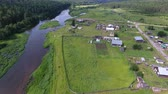 cam : Drone flies over Village and River. Flying over the village and the river forest shores in the summer. In the village there are wooden houses and tourist tents Stok Video