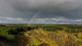 Rainbow over Forest and Field. Flight over forest and field in the fall. Ahead over the river rainbow. The landscape North of autumn nature