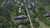 Dilapidated Houses of Dead Town. The video is taken from a quadrocopter over a dead forest. Brick houses dilapidated, the Windows had no glass, the roof is broken. The view is similar to post-apocalyptic