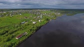 podróż : Flying over River to Town. The video is taken from a quadrocopter flying over a large Northern river. On the river Bank there is a small town. Further out of town there is a forest to the horizon