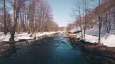 bashkortostan : Flying over a stream through a beautiful spring forest in snow