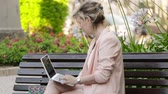 senhora : Attractive blonde white woman working freelance with laptop and smartphone in park at sunny day Vídeos