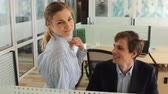 Young woman flirting with man in office Стоковые видеозаписи