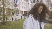 Curly haired girl in denim jacket and blue hoodie on the street.