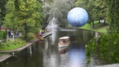 Latvia, Riga. Tourists and holidaymakers make a trip on a pleasure. The berth is decorated with a large beautiful sphere.