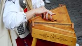 The girl in the Latvian national clothes playing the national instrument kokle on the street of Riga.
