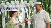 fede nuziale : happy pastafarian couple, the bride puts a wedding ring on the finger of the groom during their wedding in the forest. full hd, no sound. Filmati Stock