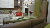 working parents : Mother and son are doing homework for school at the kitchen Stock Footage
