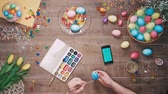 Man painting easter egg and smart phone with green screen lies on table decorated with easter eggs. Top view Stock Footage
