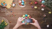 снимок : Man taking picture of basket with easter eggs on table decorated with easter eggs. Top view Стоковые видеозаписи