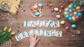 písemný : Man puts words Easter Geetings on table decorated with easter eggs. Top view