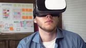Mobile app developer testing his futuristic app concept using VR headset Stock Footage