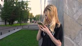 RUSSIA, MOSCOW - JULY 23, 2016: The beautiful blonde with iPhones leafing through photos in the park VDNKH Стоковые видеозаписи
