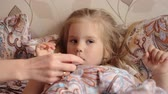 bacterial : Sick little girl lying in her bed and Mother checking temperature of her sick daughter in her mouth