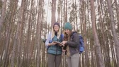 Young women with map looking for direction in forest