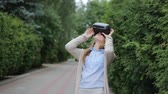 Young woman watching video by virtual reality headset. Stok Video