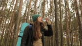 girl drinks water from a bottle on the background the forest