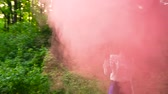 granada : Woman in beautiful clothes runs through the forest waving colored smoke
