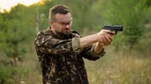arma curta : Young man in camouflage shooting from a gun, close up. Slow motion