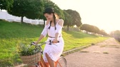 bike : Young beautiful woman riding a bicycle at sunset. Slow motion