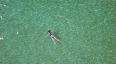 supine : Relaxed beautiful girl lies on her back in the summer sea Stock Footage