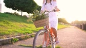 ciclismo : Young beautiful woman riding a bicycle at sunset