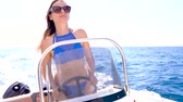 моторизованный : Summer vacation - young girl driving a motor boat on the sea. Slow motion