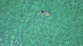 supine : View from the height on swimming woman in the clear sea