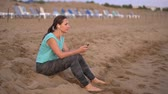 závazek : Athletic woman with headphones sits on the beach and rests after jogging. Video at different speeds - normal and slow