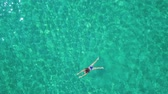 gastos : View from the height on swimming woman in the clear sea