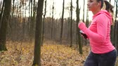 Close up of woman with headphones and smartphone running through an autumn forest at sunset. Slow motion