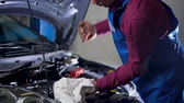 inserting : Car service, repair, maintenance and people concept - auto mechanic working at workshop Stock Footage