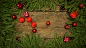 приукрашивание : Christmas decorations falling on a wooden background with fir branches and cones ready for your design. Winter holidays background
