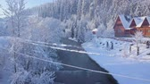 harikalar diyarı : Flight over girl walking along a bridge across a mountain river near a mountain covered with coniferous forest in winter. Clear sunny frosty weather Stok Video