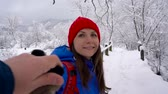 carpathians : Follow me - happy young woman pulling guys hand while walks across the bridge across the river in winter