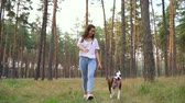 munkatársai : Girl playing with her dog in the forest at sunset. Slow motion Stock mozgókép