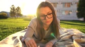 cobertor : Girl in glasses reading book lying down on a blanket in the park at sunset