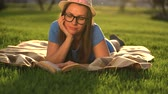 literatura : Girl in glasses reading book lying down on a blanket in the park at sunset