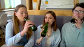 разговор : Three friends sit in a cafe, drink water or beer and have fun communicating