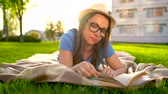 página : Girl in glasses reading book lying down on a blanket in the park at sunset