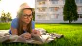 ormanda yaşayan : Girl in glasses reading book lying down on a blanket in the park at sunset