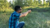 calibre : Young man is shooting from a gun, close up. Slow motion