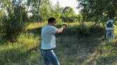калибр : Young man is shooting from a gun at the target, close up