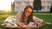 роман : Girl in glasses reading book lying down on a blanket in the park at sunset