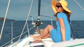 tentador : Woman in a yellow hat and blue dress girl rests aboard a yacht on summer season at ocean