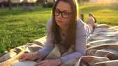 лежа : Girl in glasses reading book lying down on a blanket in the park at sunset