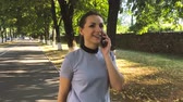 жестикулируя : Woman in talking on the smartphone while walking down the street, close up
