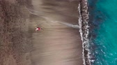 šortky : Aerial view of a man in red shorts lies on deserted black volcanic beach in a star pose. Aerial drone footage of sea waves reaching shore