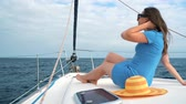 jachting : Woman in a yellow hat and blue dress rests aboard a yacht on summer season at ocean Dostupné videozáznamy