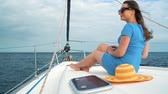 luxurious : Woman in a blue dress rests aboard a yacht on summer season at ocean. Slow motion Stock Footage